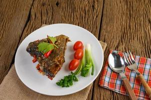 Cabeza de pescado frito cubierto con chiles en una placa blanca.