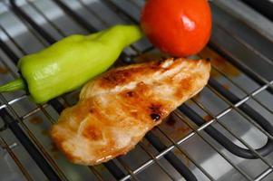 Pollo a la plancha sobre una parrilla eléctrica con pimentón y tomate