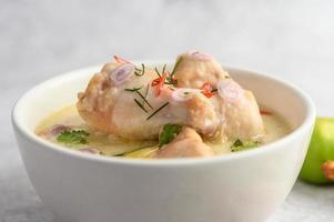 tom kha kai, sopa tailandesa de coco sobre un fondo neutro