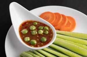 Shrimp-paste sauce in a bowl with cucumber, yard long bean and carrots