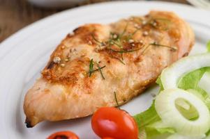 Grilled chicken on a plate with tomatoes, salad and onion