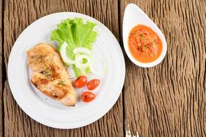 Grilled chicken on a wooden table with tomatoes, salad, onion and chili sauce