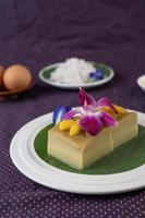 Custard on a banana leaf with pea flowers and orchids