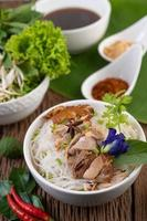 Chicken and noodles in a bowl with side dishes