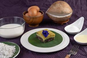 Black sticky rice on a banana leaf in a white plate with butterfly pea flowers