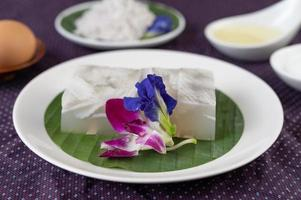 Coconut jelly on a banana leaf with butterfly pea flowers and orchids