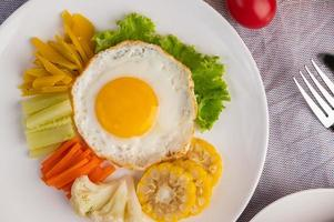 huevo frito, ensalada, calabaza, pepino, zanahoria, maíz, coliflor, tomate y tostadas
