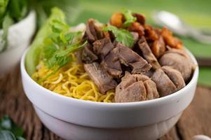 Yellow noodles with crispy pork and meatballs