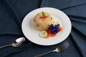Egg fried rice on a white plate with wrinkled fabric