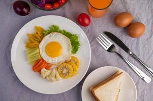 Fried egg breakfast with vegetables and juice