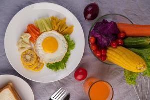 Desayuno de huevo frito con verduras y jugo.
