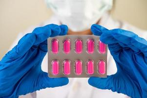 Doctor wears gloves and holds medicine panels