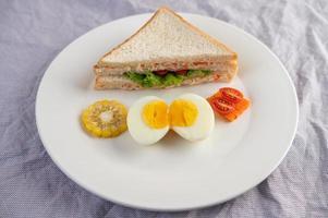 Huevos duros, maíz, sándwich de tomate en un plato blanco