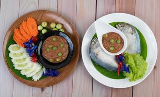 Chili paste in a bowl with mackerel and eggplant, carrots, peppers and cucumbers