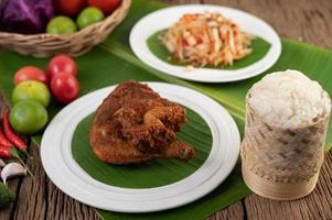 Chicken thighs fried on banana leaves with sticky rice