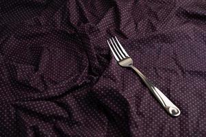 Fork on purple wrinkled fabric photo