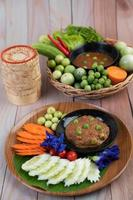 Chili paste paste in a bowl with eggplant, carrots, chili and cucumbers in a basket photo