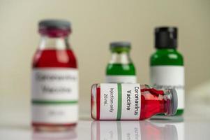 la vacuna contra el covid-19 en botellas rojas y verdes foto