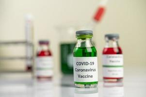 The vaccine against covid-19 in red and green bottles photo