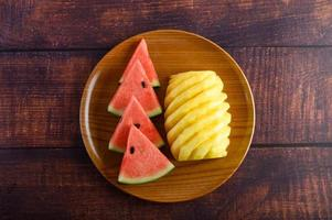 Watermelon and pineapple slices on dark wooden table