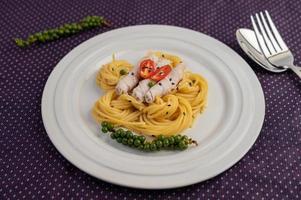 Espaguetis y cerdo plateados dispuestos en una placa blanca.