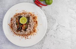 fideos cubiertos con carne de cerdo picada, pescado enlatado y limón foto