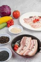 Pork belly in a pan with pepper seeds, tomatoes and spices photo