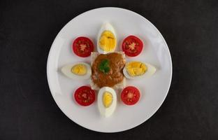 Bread topped with chili paste with boiled eggs and tomatoes