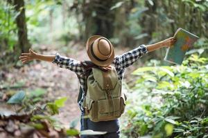 Feliz joven aventurera viendo la vida silvestre con binoculares en la naturaleza