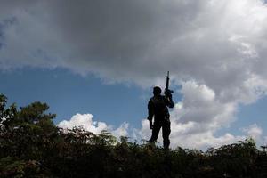 Siluetas militares de soldados con arma preparada.
