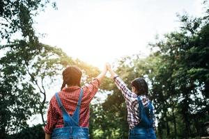 Two young girlfriends holding hands up in the air photo