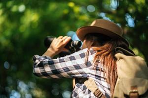 Happy adventurous young woman watching wildlife with binoculars in nature