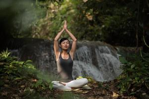 Young woman in a yoga pose sitting near a waterfall