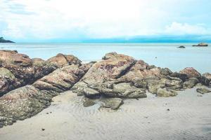 Rocks on beach with cloudy blue sky