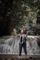 Young woman having fun under a waterfall in the forest