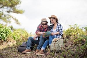 Young couple looking at map while hiking in the forest