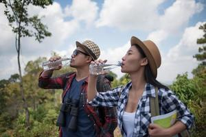 Young hikers drinking water in the forest
