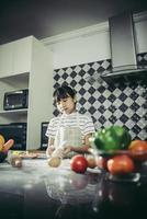 Cute little girl kneads flour dough in the kitchen