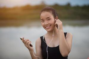 Fitness teen with earphones listening music during her workout