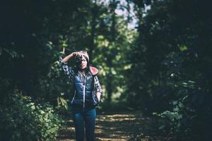 Young woman in hoodie holding a retro camera and taking photos in the forest