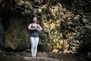 Young woman in a yoga pose near a waterfall