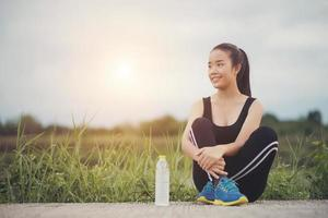 Teen fitness runner relaxing with water after training