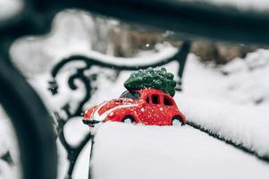 Toy red car hauling a Christmas tree on the snowy seat