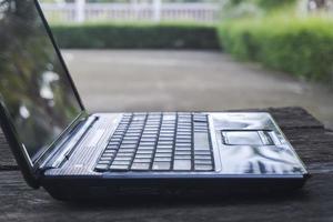 Ordenador portátil negro vacío sobre una mesa de madera foto