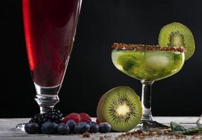 Kiwi cocktail decorated with slices and fruits of the forest on a wooden base.