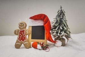 Decoraciones navideñas con pizarra sobre fondo blanco.