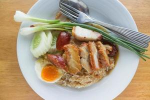 Barbecued pork and sliced boiled egg with rice and vegetables on white plate on table photo