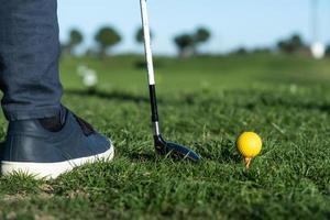 Close-up of shoes, golf club, and golf ball on a driving range