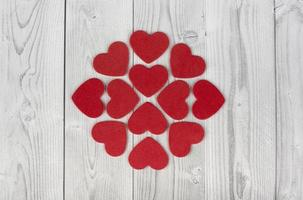 Red hearts forming a geometric figure in the centre of a white and grey wooden background. concept of valentines day