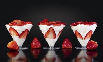 Strawberries with cream in cup on black background photo